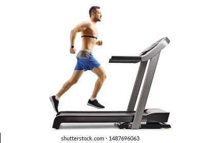 Full length profile shot of a young muscular man running on a treadmill and wearing a chest strap isolated on white background