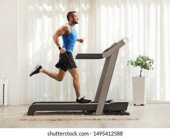 Full length profile shot of a young man running on a treadmill at home