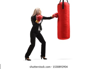 Full length profile shot of a young businesswoman punching in a boxing bag isolated on white background