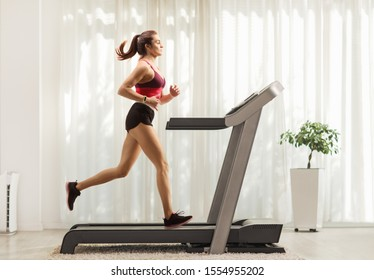 Full length profile shot of a young woman running on a treadmill at home