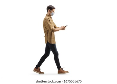 Full length profile shot of a young man with a medical face mask walking and typing on a mobile phone isolated on white background