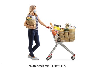 Full length profile shot a young woman with a shopping cart and a paper bag wearing a protective face mask isolated on white background