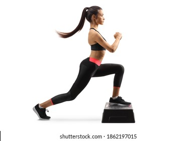 Full length profile shot of a young fit woma exercising step aerobic isolated on white background