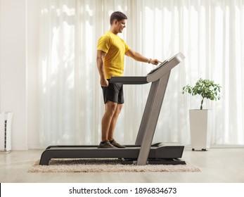 Ganzes Profilbild eines jungen Mannes in Sportbekleidung, der zu Hause einen Knopf auf einer Laufband drückt
