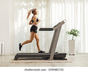 Full length profile shot of a young female exercising on a treadmill at home