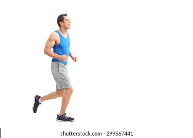 Full length profile shot of a young man in sportswear running and smiling isolated on white background