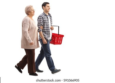 Full length profile shot of a young man holding a shopping basket and walking with a mature woman isolated on white background