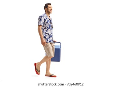 Full length profile shot of a young man holding a cooling box and walking isolated on white background