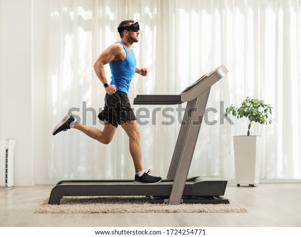 Full length profile shot of a young man running on a treadmill and wearing a vr headset at home