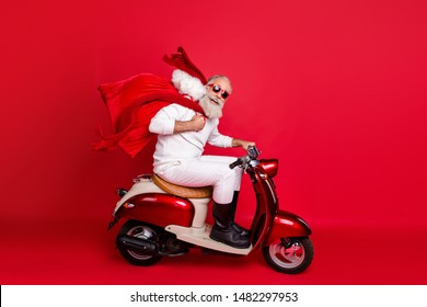 Full length profile side photo of funny pensioner carrying bag with gifts sitting on motorcycle hurrying wearing white sweater pants boots isolated over red background