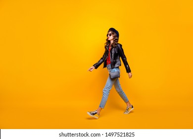 Full length profile side photo of focused gorgeous girl walk on stroll wear black leather jacket denim jeans isolated over yellow color background