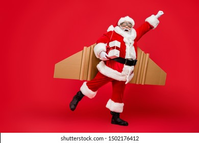 Full length profile side photo of crazy funny elderly superhero santa start launch fly up his rocket wings to give presents on christmas night wear costume cap hat isolated over red background