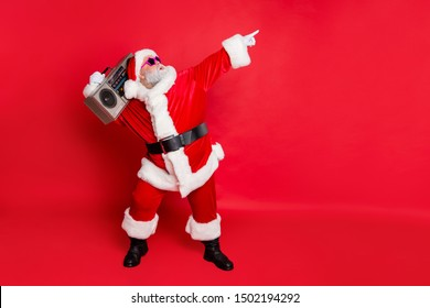 Full length profile side photo of funny santa claus raise his arms dance wear stylish trendy eyewear eyeglasses hat headwear isolated over red background