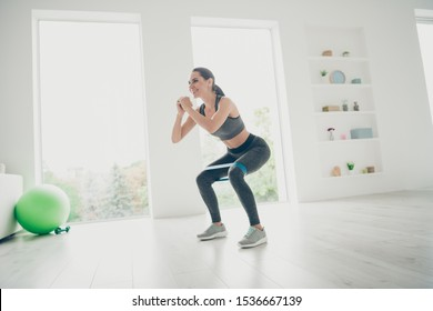 Full length profile side photo of active energetic athlete girl motivates to become strong muscular weightlifter do sport sit squats with expander wearing grey pants sneakers in gym like house