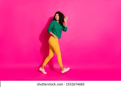 Full length profile side photo of positive curly hair afro american girl had fun on winter free time go walk hold hand say bye wear knitted jumper outfit pants sneakers isolated pink color background