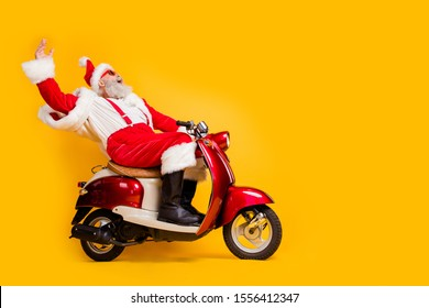 Full length profile side photo of crazy funky white bearded santa claus hipster ride fast his scooter hurry on christmas x-mas wear shirt suspenders isolated over yellow color background