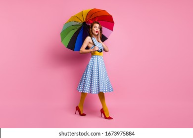 Full length profile side photo astonished woman go hold shine umbrella look gossip rumors scream oops hurry tell buddy wear blue polka-dot tights high-heels isolated pink color background