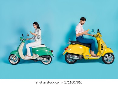Full length profile side photo of positive two people bikers driver drive yellow green choppers use cellphone search gps location wear trousers shirt isolated blue color background