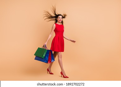 Full length profile side photo of pretty girl walk fly hair hold bags wear red dress short skirt isolated on beige color background