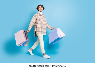 Full length profile side photo of young girl happy smile hold bags go shopping isolated over blue color background