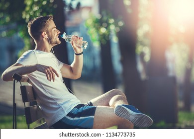 Full length profile of smiling man sitting on bench and drinking water. He is satisfied with morning workout