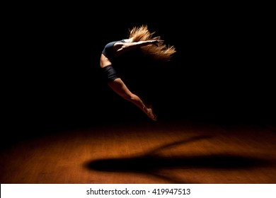 Full length profile view of a gorgeous female jazz dancer jumping during a performance in a dark stage under a spotlight