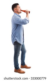 Full length profile view of a young Hispanic man drinking beer from a bottle against a white background