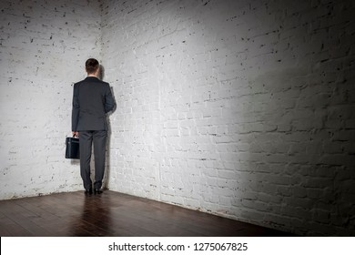 Full length rear view of businessman standing in corner at office