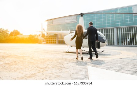Full length rear view of businessman in suit dragging his luggage hold women hand walking hurry towards Helicopter platform.Long trip working of executive man and woman with helicopter.Business trip.