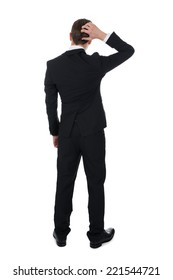 Full length rear view of confused businessman scratching his head over white background