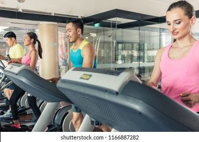 Full length rear view of a fit active woman running on treadmill during workout session in a trendy fitness club with modern equipment