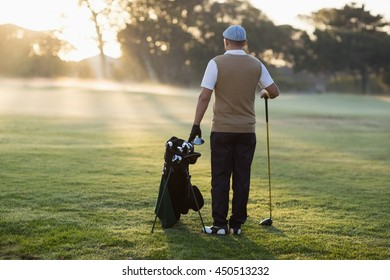 Full length Rear view of golfer standing on grassy field