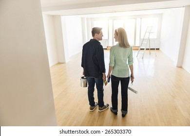 Full length rear view of mature couple with paint equipment standing at home