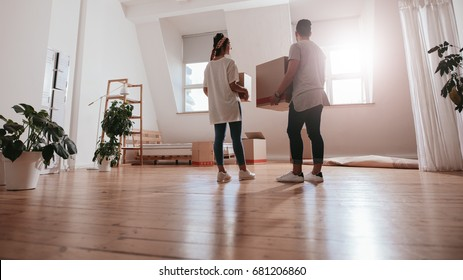 Full length rear view shot of young couple carrying cardboard box at new home. Young man and woman holding boxes and moving in new house.