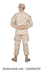 Full length rear view studio shoot or army soldier in camouflage uniform and utility cover, standing in parade rest position with legs on shoulder width and hands behind back isolated on white