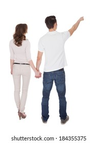 Full length rear view of young man pointing while holding woman's hand isolated over white background
