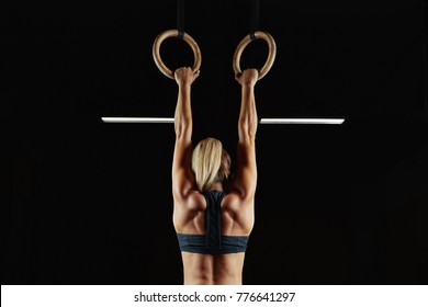 Full length rearview shot of a female athlete performing pull-ups on gymnastic rings. Fitness and crossfit woman with strong beautiful body exercising on gym rings health power endurance competitive