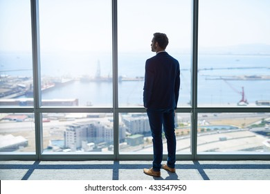 Full length rearview of a young stylish businessman standing at the large windows of a high office, looking at the view of a harbour below