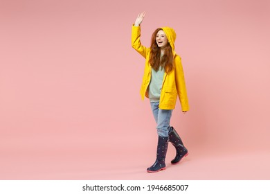 Full length redhead fun young woman in yellow waterproof hood raincoat outerwear walk go waving hand greet isolated on pastel pink background studio Outdoors lifestyle wet fall weather season concept
