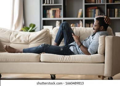 Full length relaxed young african ethnicity man in glasses lying on comfortable couch, enjoying spending weekend leisure time chatting in social network on phone with friends, watching funny videos.