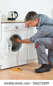 Full length of repairman checking washing machine with digital multimeter at home