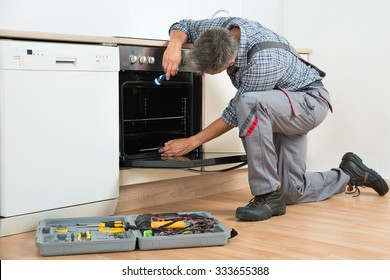 Full length of repairman examining oven with flashlight in kitchen
