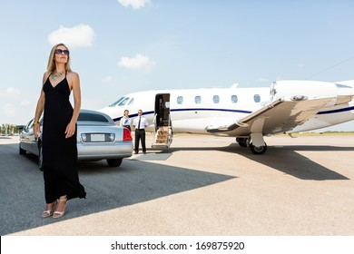 Full length of rich woman in elegant dress standing against limousine and private