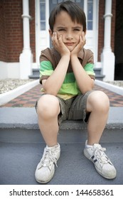 Full length of sad little boy with hands on chin sitting on front steps of house