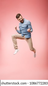 Full length of a satisfied young man jumping and celebrating success isolated over pink background