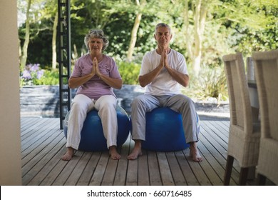 Full length of senior couple meditating together while sitting on exercise balls at porch