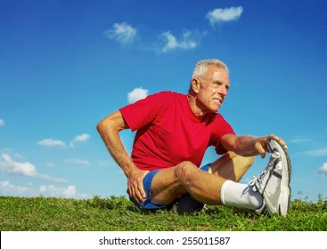 Full length of senior man in pain while stretching leg on meadow