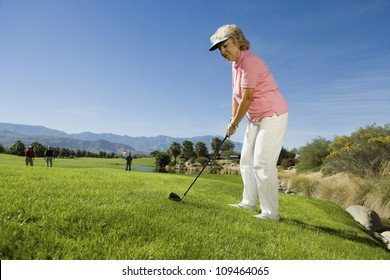 Full length of a senior woman playing golf with people in the background