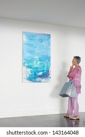 Full length of senior woman with shopping bags observing painting in art gallery