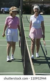 Full length of a senior women standing at net on tennis court